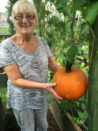 Janet who was showing me around holding the pumpkin for scale - it probably won't be around for Halloween!
